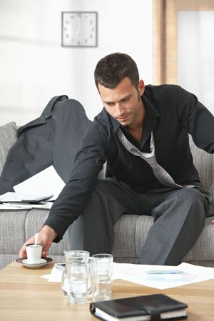 People at office. Tired businessman sitting on sofa looking at documents drinking coffee. Stock Photo - 5766900