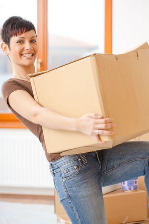 levantar peso: Mujer de elevaci�n caja de cart�n, mientras que la mudanza, sonriendo. Foto de archivo