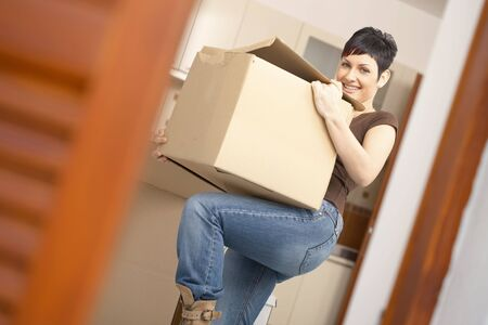 migrate: Woman lifting cardboard box while moving home, smiling.
