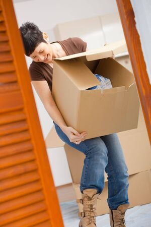face lift: Woman lifting cardboard box while moving home, smiling.