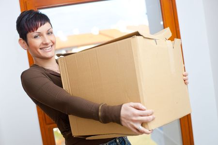Woman lifting cardboard box while moving home, smiling. Stock Photo - 5767366