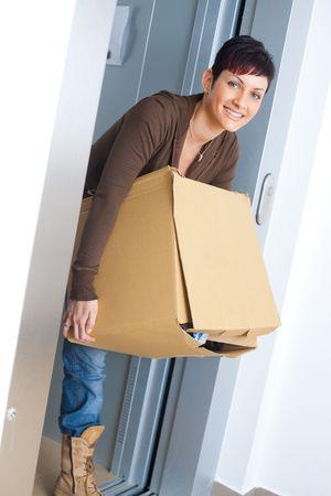 boite carton: Jeune femme transportant une bo�te en carton de lever pendant le d�m�nagement � la nouvelle maison.