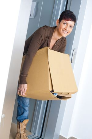 Young woman carrying cardboard box out of lift during moving to new home. photo