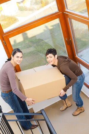 Two young women carrying up cardboard box on staircase to new home.