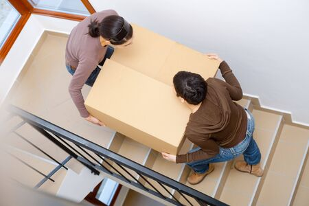 lift and carry: Two young women carrying up cardboard box on stariway to new home. Stock Photo
