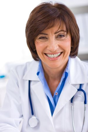 Portrait of happy senior female doctor at office, smiling. photo