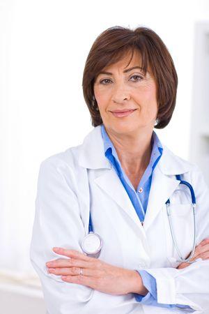 doctora: Retrato de feliz m�dico femenino de nivel superior en la oficina, sonriendo.