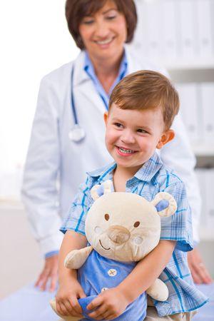 Senior female doctor examining happy child, smiling. Stock Photo - 5767356