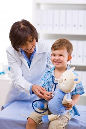 child to the doctor: Senior female doctor examining happy child, smiling.