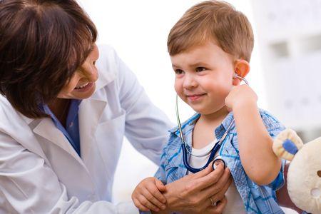Senior female doctor examining happy child, smiling. Stock Photo - 5767352