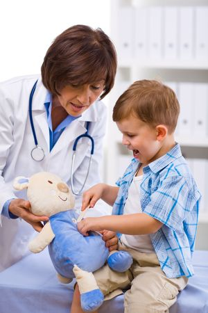 Senior female doctor and happy child examining teddy bear. photo