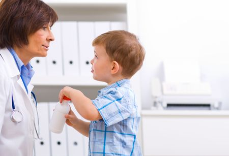 check room: 3 years old boy playing with senior female doctor at office.
