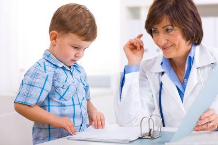 ni�os enfermos: Pediatra Senior femenino jugando con los ni�os a los m�dicos de oficina.