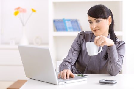 Young woman drinking coffe while shopping online using her laptop. Stock Photo - 5767100