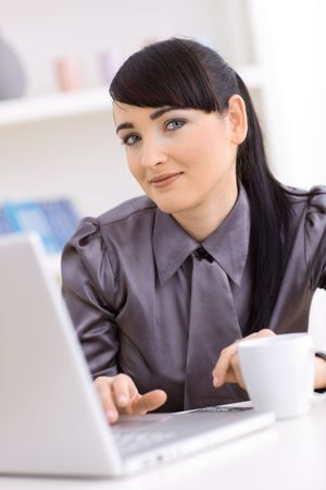 Young businesswoman working on laptop at home. photo