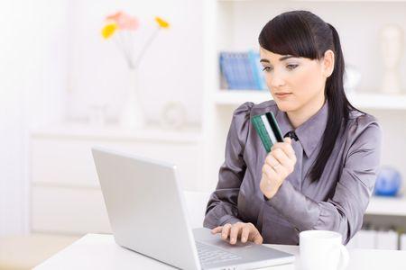 Les jeunes femmes des achats en ligne à la maison, en utilisant un ordinateur portable, la détention de cartes de crédit en main en mettant l'accent à l'écran.