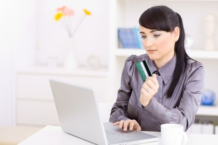 Young women shopping online at home, using laptop computer, holding credit card in hand focusing at screen. photo