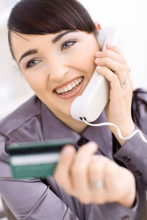 Closeup portrait of smiling young women shopping online at home, holding credit card in hand and talking on phone. photo