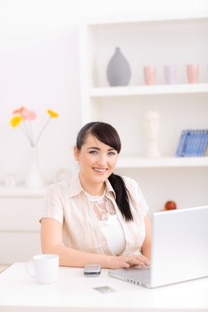Young woman working at home typing on a laptop computer, smiling and looking at camera. Stock Photo - 5767341