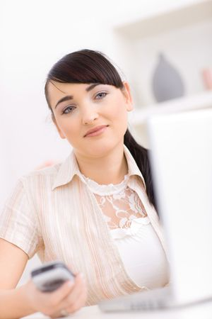 Young woman working at home, holding a mobile phone in hand, smiling. photo