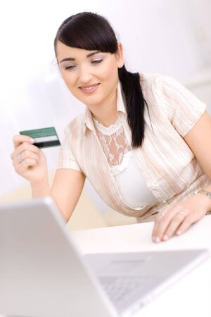 Smiling young women shopping online at home, using laptop computer, holding credit card in hand. photo
