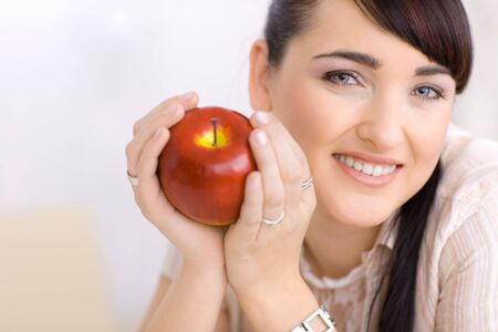 Closeup portrait of beautiful young woman holding red apple in hands, smiling happily. photo