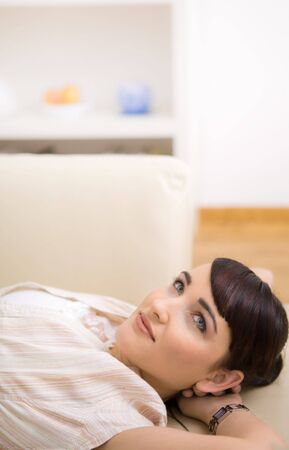 snug: Young woman resting on a couch at home, smiling. Stock Photo