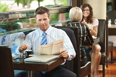 Businessman sitting at table in cafe, reading newspaper and drinking coffee. Young women talking in the background. photo
