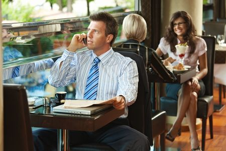 Businessman sitting at table in cafe, reading newspaper and talking on mobile phone. photo