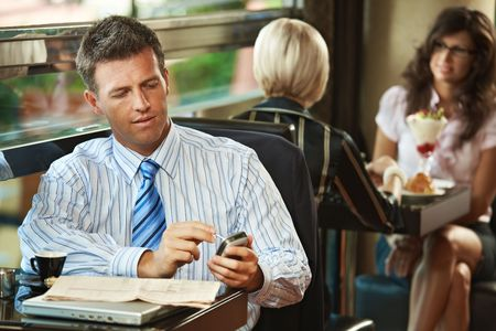 Businessman sitting at table in cafe using mobile phone. Young women having sweets in the background. photo