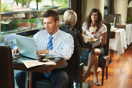 Businessman sitting at table in cafe using laptop computer. Young women having sweets in the background. photo