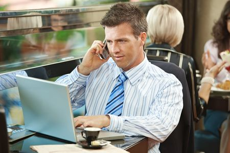 Businessman sitting at table in cafe using laptop computer, talking on mobile.  photo