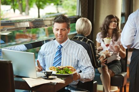 Businessman sitting at table in cafe, eating club sandwich and  using laptop computer. Waiter serving sweets in the background. photo