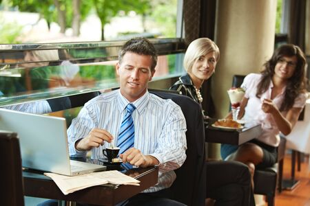 Businessman using laptop in cafe, young women in the background recognized him. Selective focus on businessman. photo