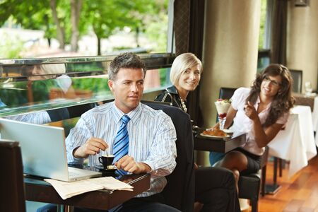 recognized: Businessman using laptop in cafe, young women in the background recognized him. Selective focus on businessman.