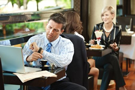 Businessman sitting at table in cafe, waiting for somebody looking at his watch. Young women having sweets in the background. photo