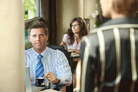 Young businessman waiting at cafe table drinking coffee,  businesswoman arriving for the meeting.  photo