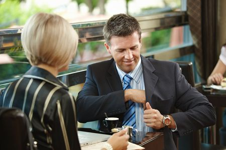 Young businessman and businesswoman sitting at table, having a meeting in cafe. photo