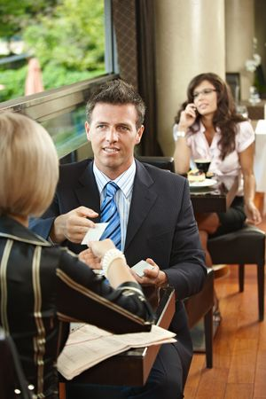 Young businessman and businesswoman having a meeting in cafe, exchanging business cards. photo