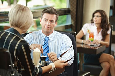 Young businessman and businesswoman having a meeting in cafe. photo