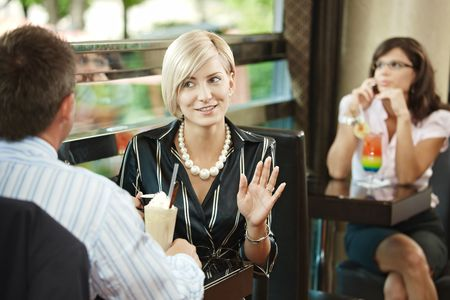 Young businessman and businesswoman sitting at table in cafe, talking. photo