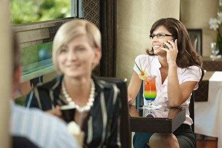 Young businesswoman sitting at table in cafe, talking on mobile phone, drinking cocktail. photo