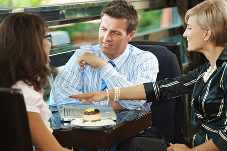 Young businessman and businesswomen having a meeting in cafe. photo