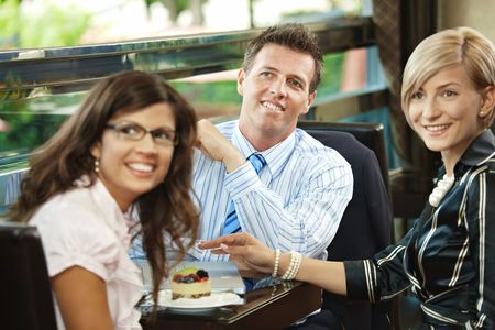 Young businessman and businesswomen having a meeting in cafe, smiling and greeting somebody. photo
