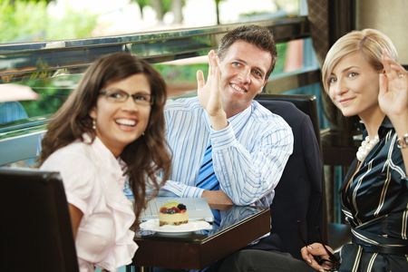Young businessman and businesswomen having a meeting in cafe, smiling and waving to somebody. photo