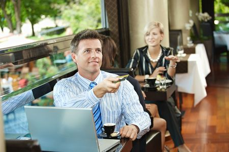 Businessman sitting at coffe table in cafe, paying with credit card, smiling. photo
