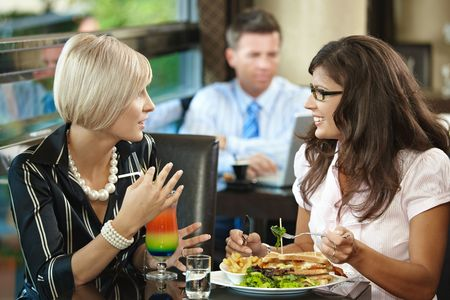 Young women sitting at table in cafe, eating sandwich and drinking cocktail, talking. photo
