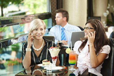 Young women sitting in cafe having sweets, talking on mobile phone. Stock Photo - 5783766