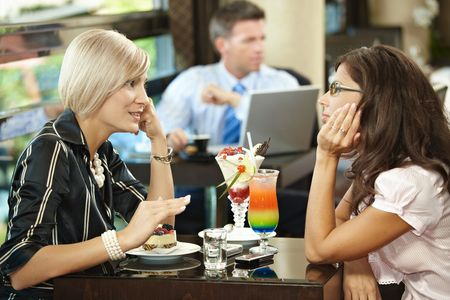 Young women sitting at coffee table in cafe having sweets, talking. photo