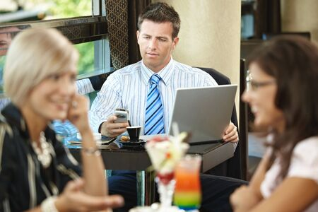 Businessman using laptop and mobile in cafe, young woman eating sweets and talking in the foreground. Selective focus on businessman. photo